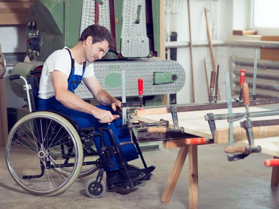 Travailleur en chaise roulante dans un atelier de menuiserie