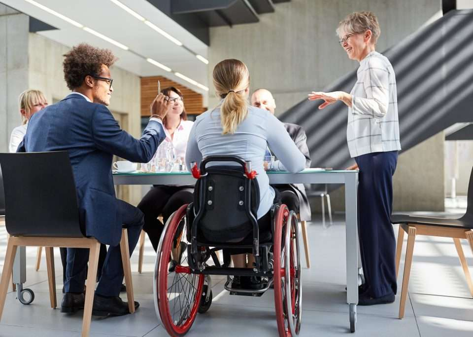 A woman in a wheelchair is seated at a table with colleagues during a work meeting.